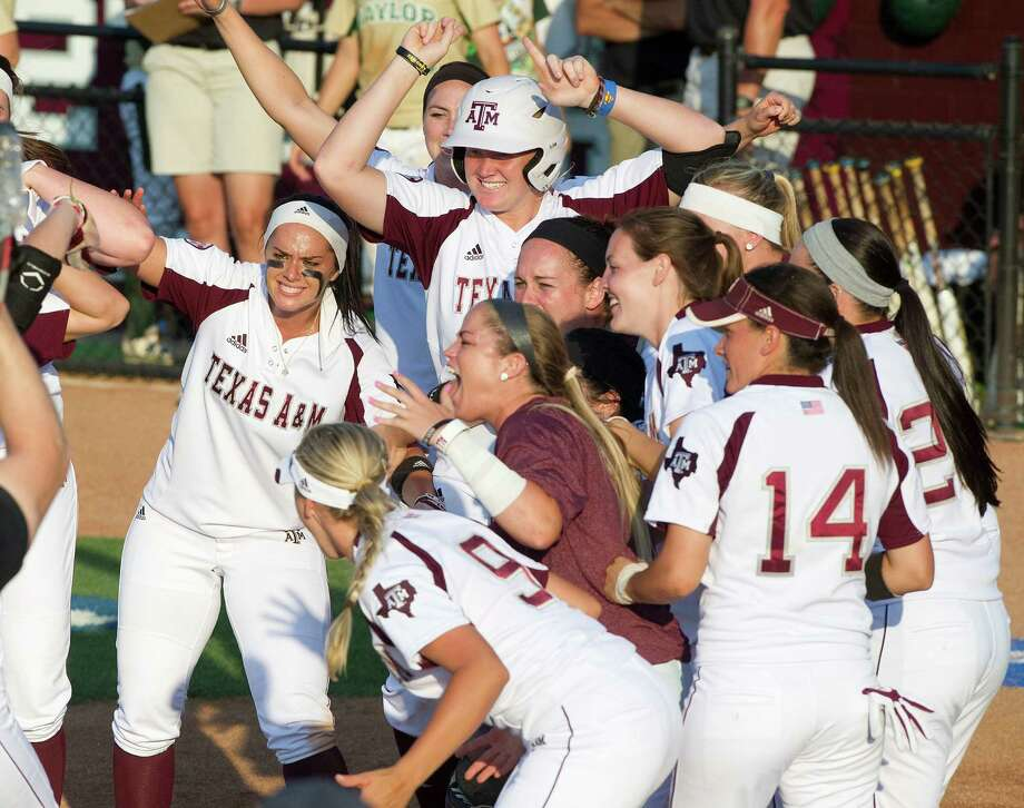A&M players swarm to home plate to greet Cali Lanphear after her home run in the fifth inning provided the final blow in the Aggies' run-rule victory. Photo: Stuart Villanueva, MBR / Bryan College Station Eagle