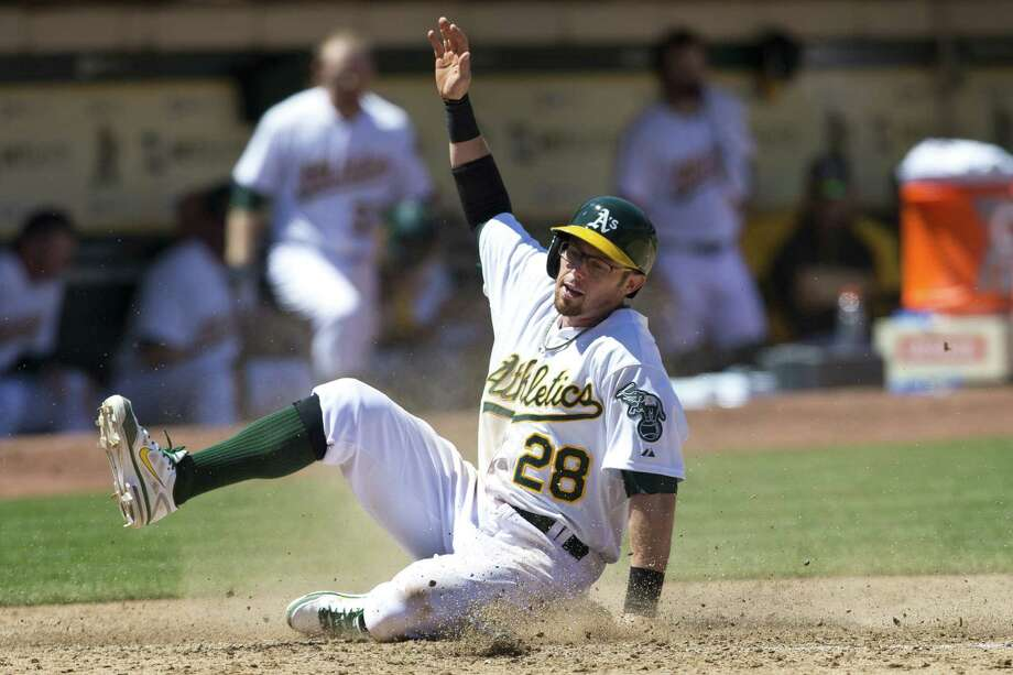 The Athletics' Eric Sogard slides into home to score against the Royals during the fifth inning. Photo: Jason O. Watson / Getty Images