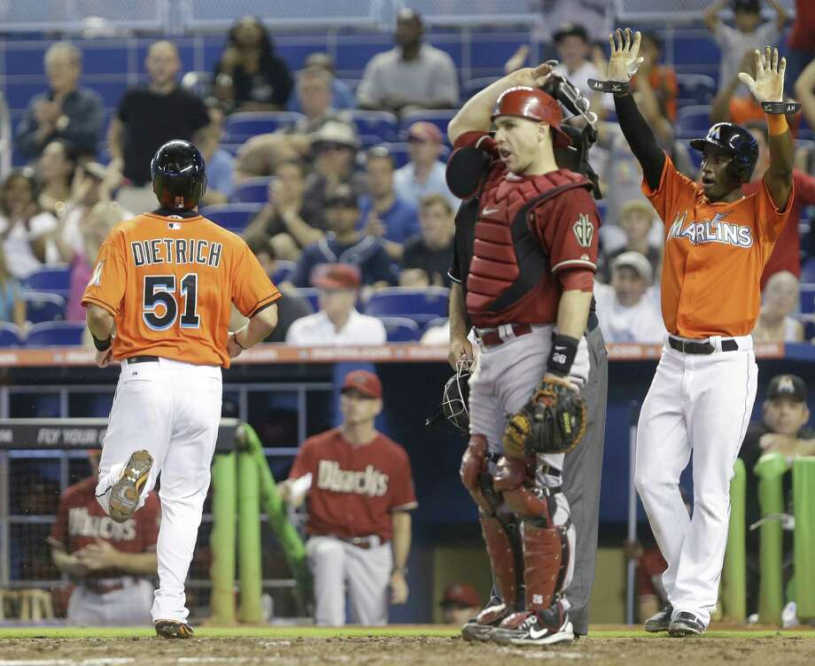 Adeiny Hechavarria (right) gestures as Derek Dietrich scores while Miguel Montero looks on. Photo: Wilfredo Lee / Associated Press