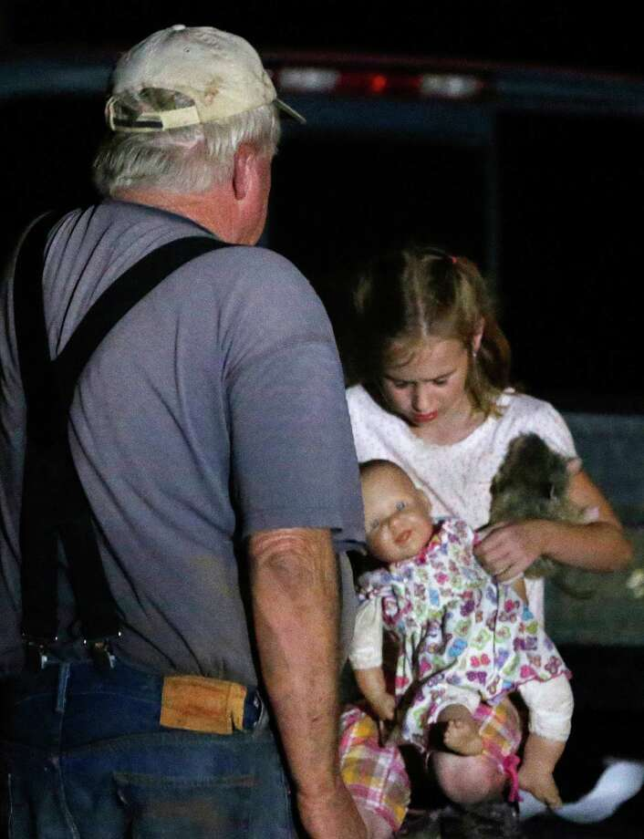 Seven-year-old Katrina Ash, right, holds a doll as she waits with her grandfather, Michael Bowen, left, after a tornado ripped through their neighborhood near Dale, Okla., Sunday, May 19, 2013. Residents are not being allowed back into the neighborhood as search and rescue efforts take place. (AP Photo Sue Ogrocki) Photo: Sue Ogrocki, Associated Press / AP
