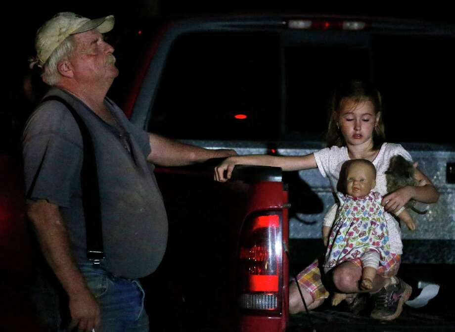 Seven-year-old Katrina Ash, right, holds a doll as she waits in the back of a truck with her grandfather, Michael Bowen, left, after a tornado ripped through their neighborhood near Dale, Okla., Sunday, May 19, 2013. Residents are not being allowed back into the neighborhood as search and rescue efforts take place. (AP Photo Sue Ogrocki) Photo: Sue Ogrocki, Associated Press / AP