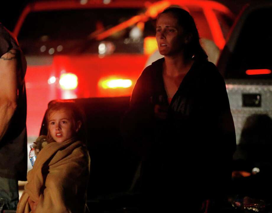 Seven-year-old Katrina Ash, left, watches with her mother, Amber Ash, right, as heavy equipment is brought into their tornado damaged neighborhood near Dale, Okla., Sunday, May 19, 2013. Residents are not being allowed into the neighborhood as search and rescue operations continue. (AP Photo Sue Ogrocki) Photo: Sue Ogrocki, Associated Press / AP