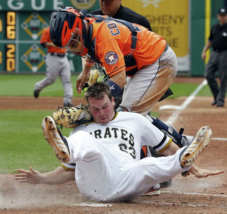 The Pirates' Travis Snider rolls into Astros catcher Jason Castro after being tagged out in the sixth. Photo: Keith Srakocic / Associated Press