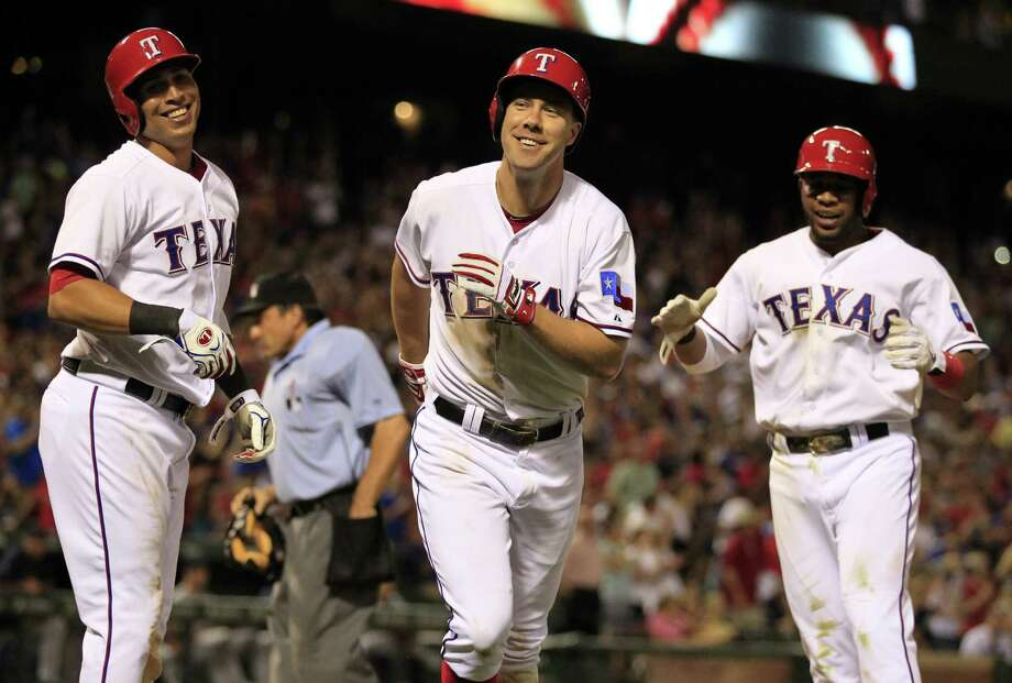 Leonys Martin (from left), David Murphy and Elvis Andrus smile after Murphy's three-run homer in the sixth inning Sunday in Arlington. The Rangers took three of four from the Tigers. Photo: Photos By John F. Rhodes / Associated Press