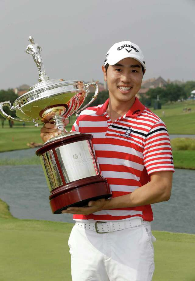 Sang-Moon Bae of South Korea holds the trophy on the 18th green after winning the Byron Nelson golf tournament Sunday, May 19, 2013, in Irving, Texas. (AP Photo/Tony Gutierrez) Photo: Tony Gutierrez, STF / AP