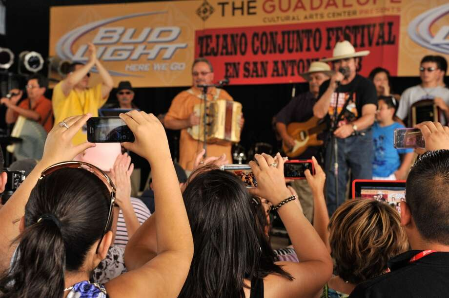Many in the crowd take pictures of Chalito Johnson y Los Paisanos as they are introduced by Juan Tejeda (at mic on right) during the 32nd Annual Tejano Conjunto Festival on Sunday afternoon, May 19, 2013.