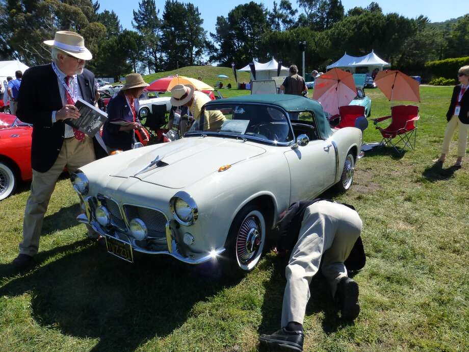 Judges scrutinizing a 1958 Fiat 1200 TV Spider owned by Ralph Moceo of Santa Cruz, Calif.