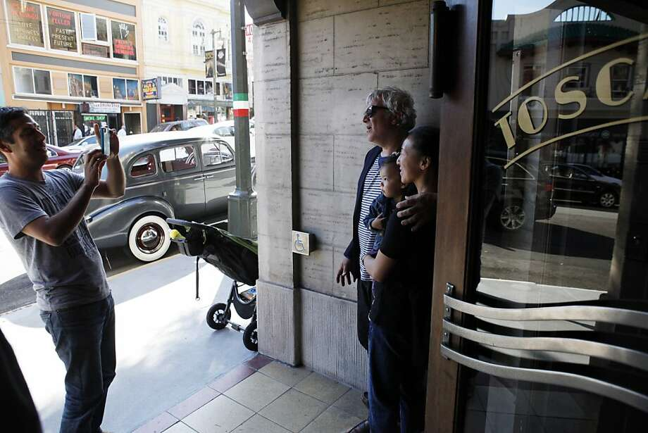 Joe Ragazzo and Tina Derentz, have their picture take with their daughter Zoe Ragazzo, by Garrick Ramirez, outside Tosca Cafe on Sunday. The couple met at Tosca and have a child. Tosca Cafe in San Francisco, Calif., will be closing for a renovation and crowds gathered out the door to bid the San Francisco icon farewell on Sunday, May 19, 2013. Photo: Carlos Avila Gonzalez, The Chronicle