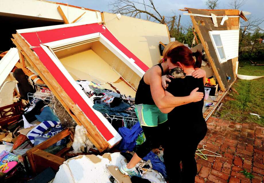 Alli Christian, left, returns Jessica Wilkinson's dog Bella to her after finding her among the wreckage of Wilkinson's home shortly after a tornado struck near 156th street and Franklin Road on Sunday, May 19, 2013  in Norman, Okla. No one was in the home when the storm struck. Photo: The Oklahoman, Steve Sisney
