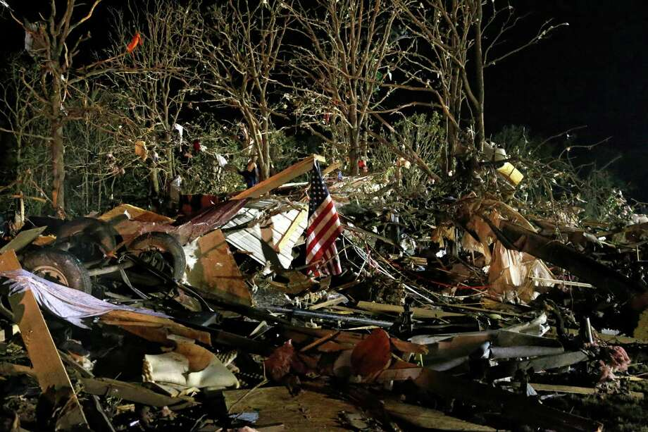 A flag flies in the debris of a mobile home after a tornado struck a mobile home park near Dale, Okla., Sunday, May 19, 2013. Photo: AP