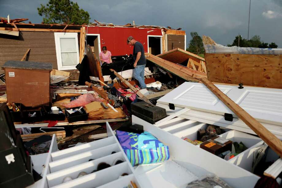 Nancy and Jason Townsend sort through belongings after their home was hit by a tornado in Carney Okla., on Sunday, May 19, 2013. The Townsend's left their home to avoid the tornado. Photo: The Oklahoman, Bryan Terry