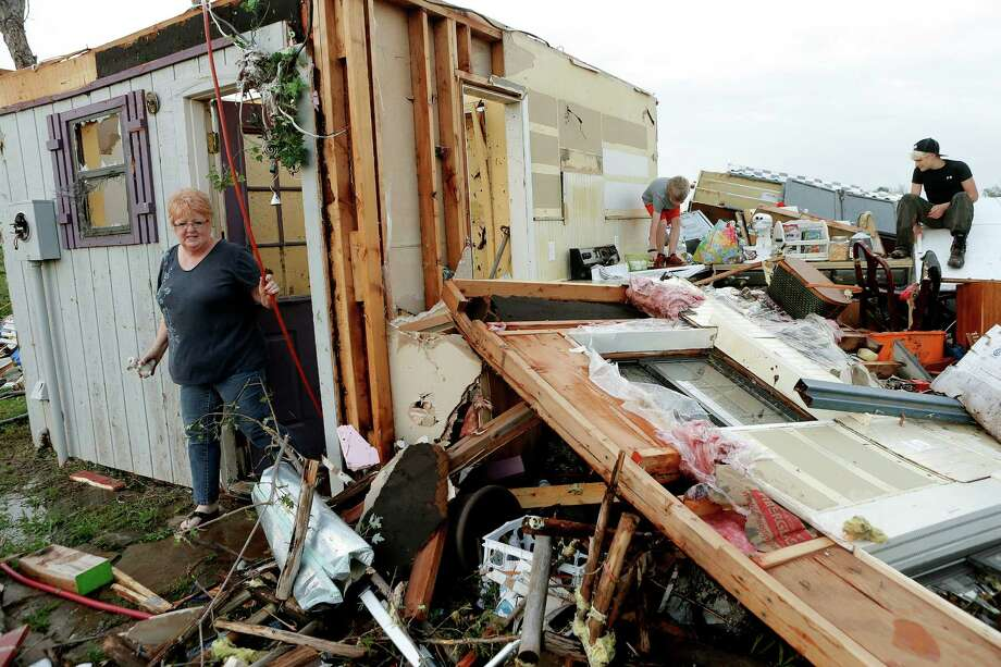 Marlena Hodson walks out of her home as her grandsons, Campbell Miller, 10, and Dillon Miller, 13, at right, help her sort through belongings after a tornado damaged her home Carney Okla., on Sunday, May 19, 2013. Hodson and her family left the home to escape the tornado. Photo: The Oklahoman, Bryan Terry