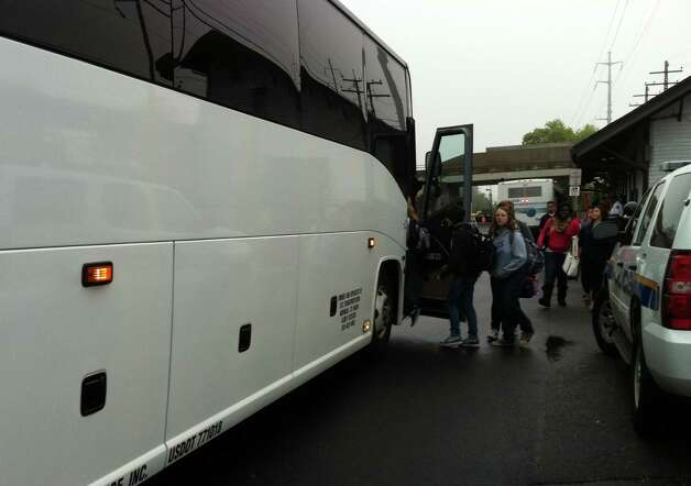 Commuters scramble aboard one of the buses carrying would-be Metro-North riders from the Fairfield Center station to Westport, where limited service to New York City is running early Monday. Photo: Genevieve Reilly / Fairfield Citizen