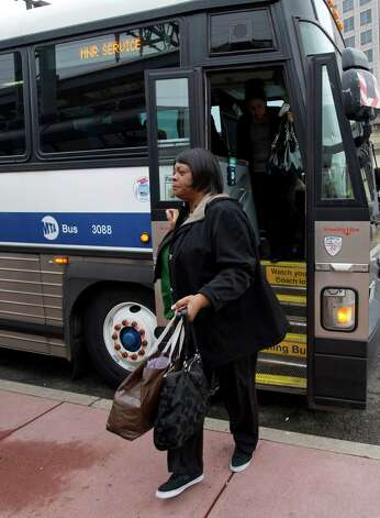 Esther Flemings disembarks a bus at the train station in Stamford, Conn., on Monday, May 20, 2013. Flemings, a Bridgeport resident, said she usually takes the train from Bridgeport to Grand Central Station but had to take the bus to Stamford due to the train derailment. Photo: Lindsay Perry / Stamford Advocate