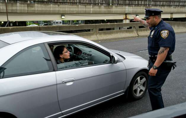 A police officer directs a driver to a drop-off location at the train station in Stamford, Conn., on Monday, May 20, 2013. Photo: Lindsay Perry / Stamford Advocate
