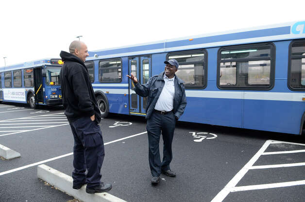 Bus drivers Emiliano Rodriguez, left, Hartford, and Paul Francis, West Hartford, wait for passengers at the Fairfield Metro train station on Monday morning, May 20, 2013. They had reported to work at 2:45am so they could offer bus service to commuters who would typically take the train, which was not serving Fairfield due to Friday's crash. The station was less crowded than usual. Photo: Shelley Cryan / Shelley Cryan for the CT Post/ freelance Shelley Cryan