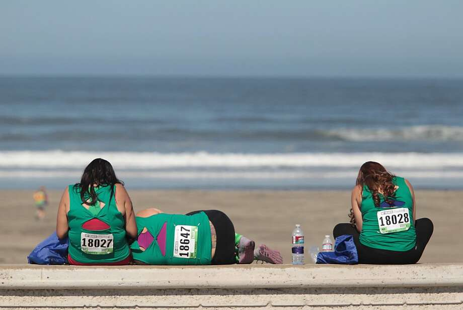 Runners Ursula Ramirez, left, Yessie Ledesma, center, and Mayra Polanco rest at Ocean Beach after completing the Bay to Breakers in San Francisco on Sunday, May 19, 2013. Photo: Mathew Sumner, Special To The Chronicle