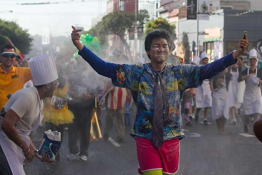 Aldo Atienza, a student at Santa Clara University, gets doused with flour during the 2013 Bay to Breakers in San Francisco, Calif. on May 19, 2013. Photo: Douglas Zimmerman, SF Gate