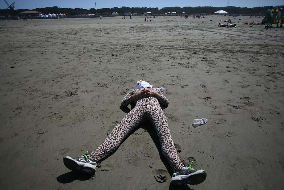 A participant rests on Ocean Beach at the finish of the Bay to Breakers in San Francisco on Sunday, May 19, 2013. Photo: Mathew Sumner, Special To The Chronicle