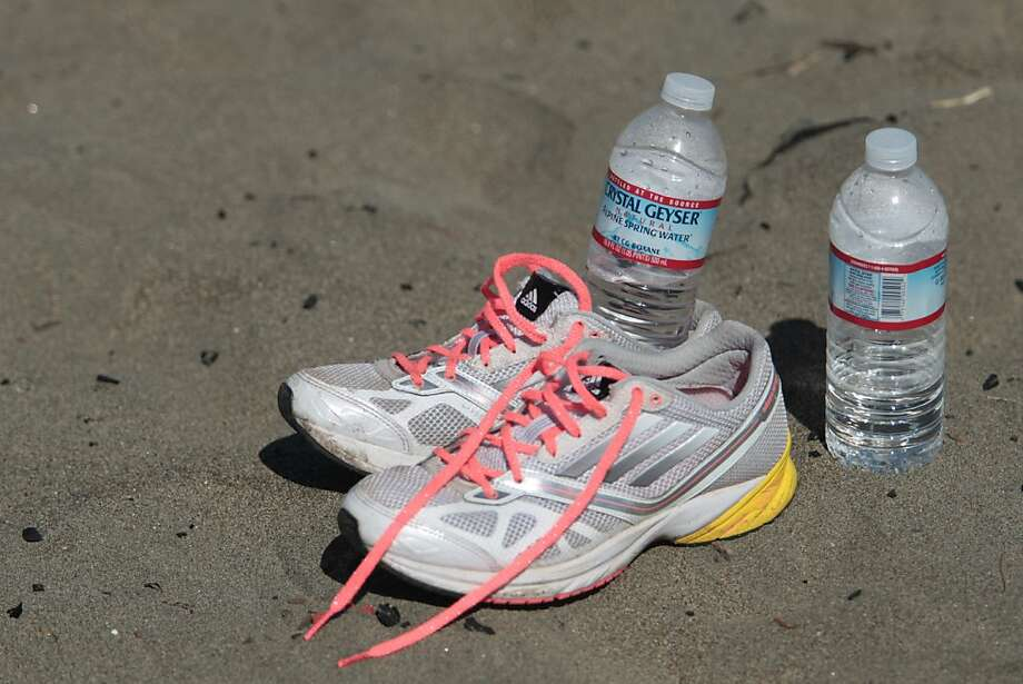 A pair of running shoes bottles of water sit on Ocean Beach after the Bay to Breakers in San Francisco on Sunday, May 19, 2013. Photo: Mathew Sumner, Special To The Chronicle