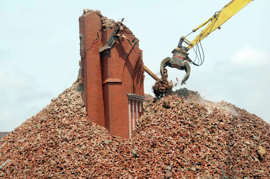 Crews pick apart the bricks as the demolition of the former St. Patrick's Church continued on Monday