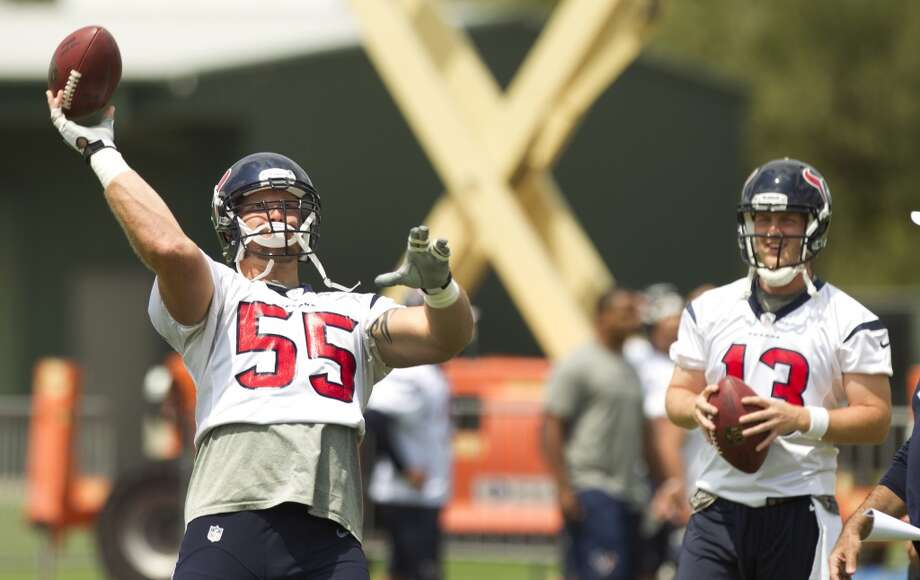Texans center Chris Myers (55) throws a pass as quarterback T.J. Yates looks on Monday at the Methodist Training Center.