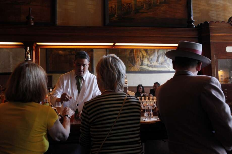 Ernie Evangelista mixes drinks for patrons at Tosca on Sunday. This week, there is no more of the familiar clink-clink of the spoons mixing the House Cappuccinos,