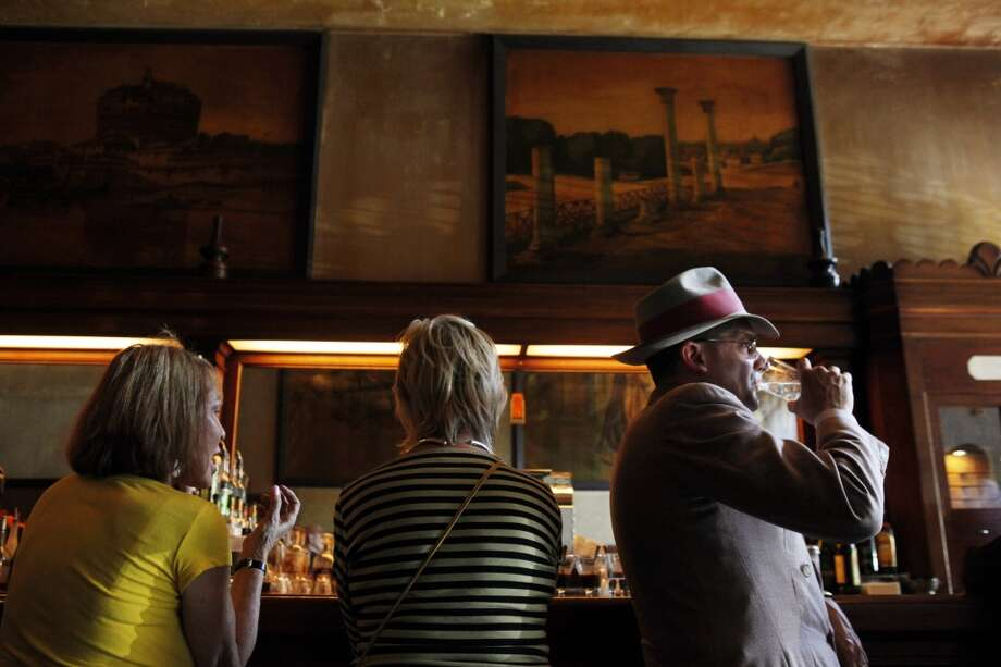Johnny Stokes, right, takes a drink on Sunday as the nicotine-stained walls loom in the backdrop.
