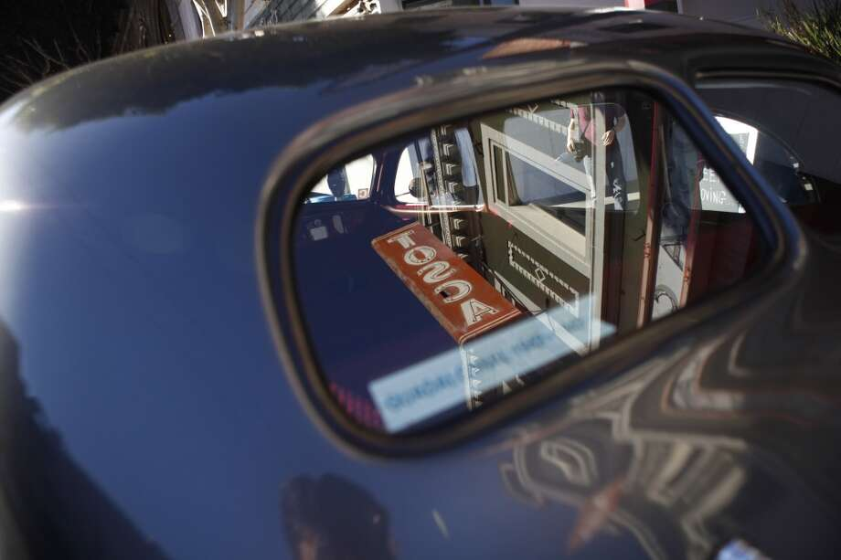Tosca's sign is reflected in a 1937 Buick Special that patron Johnny Stokes of San Francisco regularly drives to the bar. The car was parked outside the bar for much of the weekend.