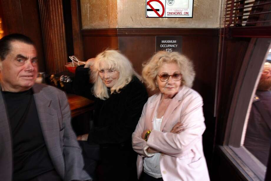 Jeannette Etheredge, owner of Tosca, poses for a photo with Carol Doda, center, and Dick Winn, at the bar in San Francisco bar on Sunday. Doda has been a regular at Tosca since she performed on Broadway years ago, when she used to pop in for a drink in between sets. The seat above -- by the windows -- was her regular seat.