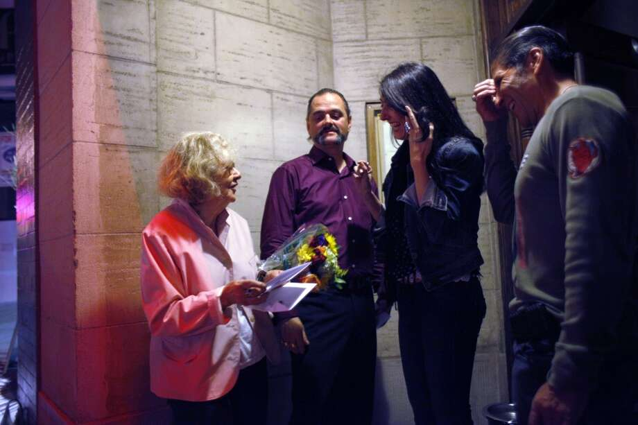Jeannette Etheredge, owner of Tosca, talks with Walter Miranda, right, and Catalina Quijano after they gave her a bouquet of flowers last night.