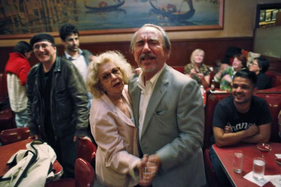 Jeannette Etheredge, owner of Tosca, dances with comedian Will Durst.