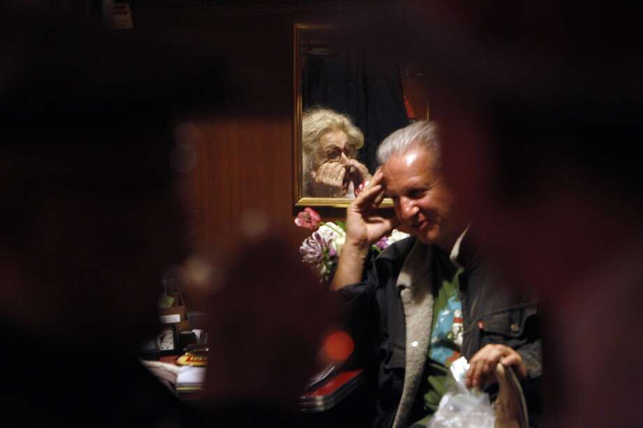 Jeannette Etheredge, owner of Tosca (seen in mirror), rubs her eyes as she speaks with Dale Djerassi.