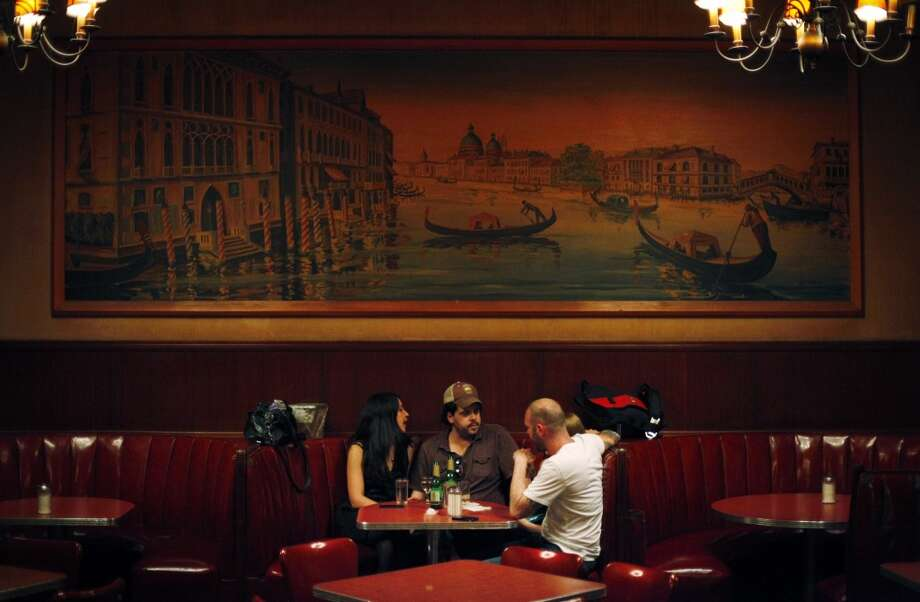 Four customers sit at a booth under one of the remaining paintings at Tosca Cafe as the famed San Francisco bar pours its last drinks in the early hours Monday.