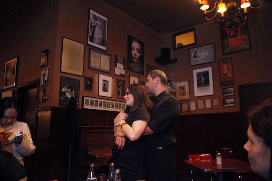Devin and Deb Etheredge hug beneath a backdrop of Tosca Cafe's photos and posters as the famed San Franciso bar closed in the early hours Monday.