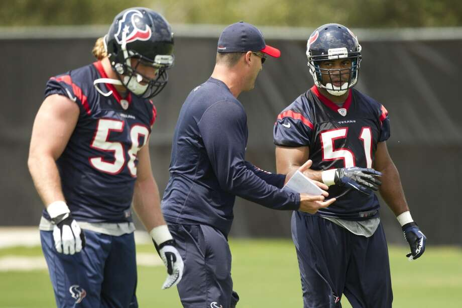 Texans linebackers Brooks Reed (58) and Darryl Sharpton (51) work with assistant linebackers coach Bobby King, center.