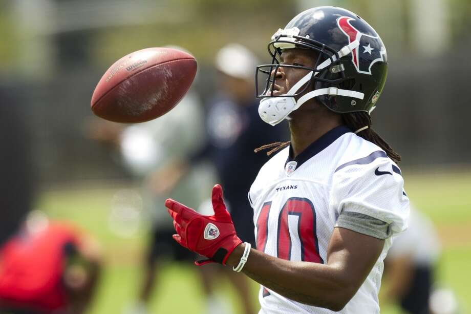 Texans wide receiver DeAndre Hopkins flips a ball in the air.
