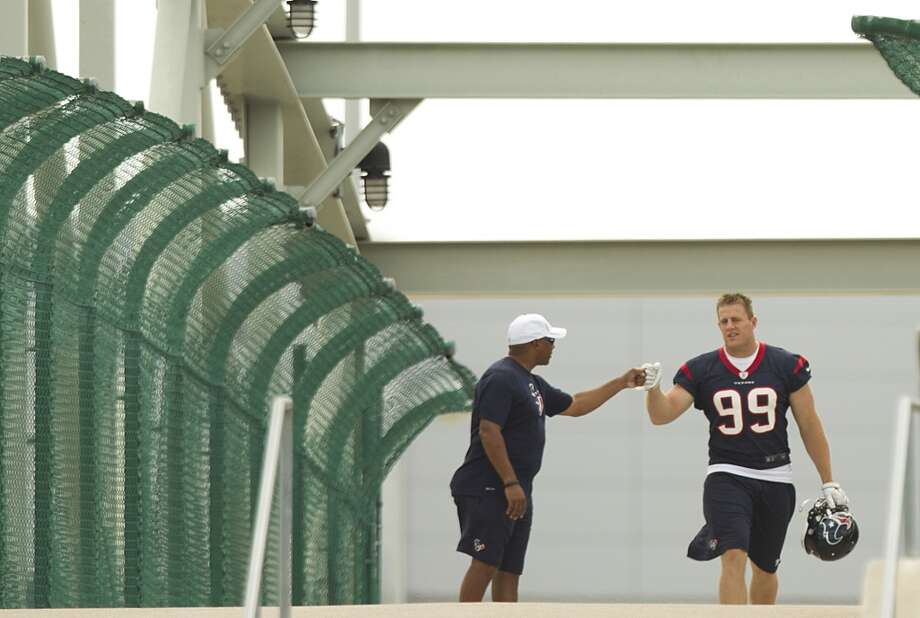 Texans defensive end J.J. Watt (99) fist bumps Emmett Baylor, director of security for the Texans, as he walks across a bridge to the practice field.