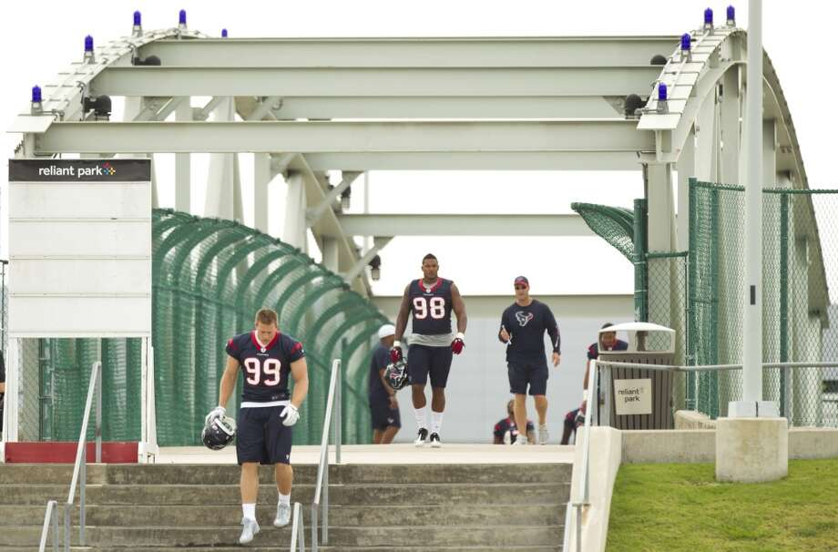 Texans defensive ends J.J. Watt (99) and Keith Browner (98) walk across a bridge to the practice field.