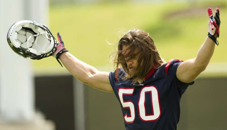 Texans linebacker Bryan Braman raises his hands as he walks across the practice field.