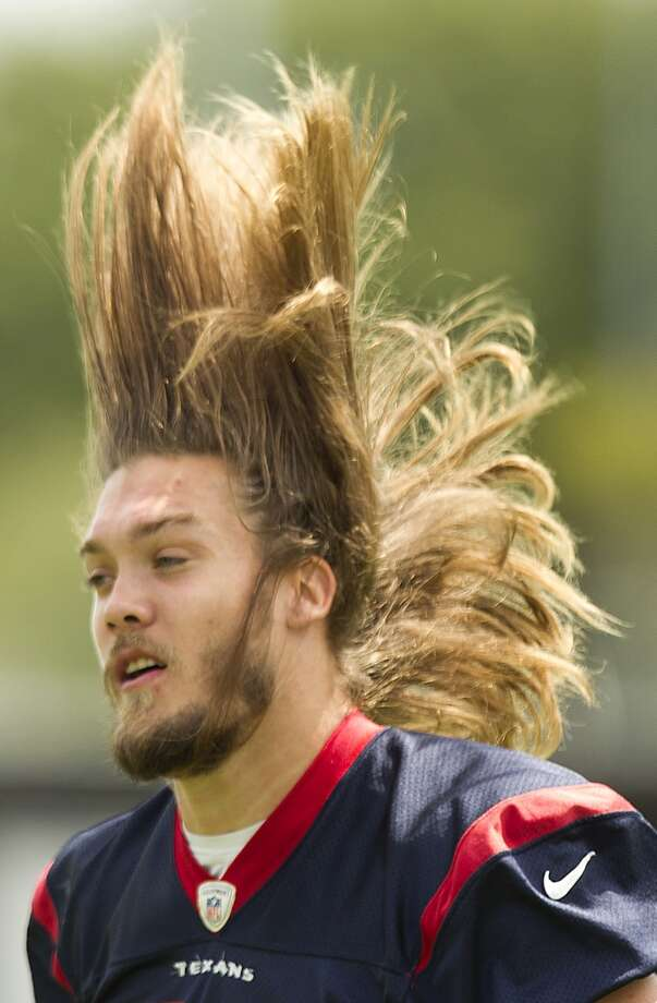 Texans linebacker Bryan Braman flips his hair as he walks across the practice field.