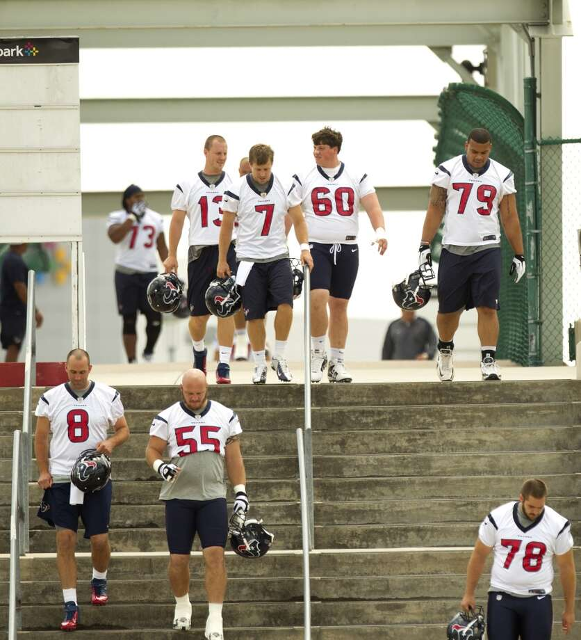 Texans players walk across a bridge to the practice field.