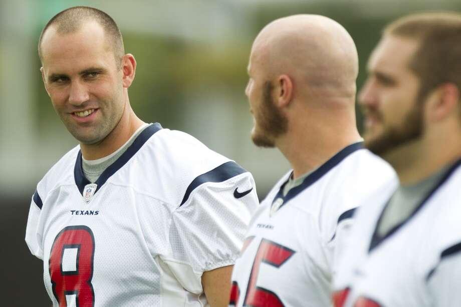 Texans quarterback Matt Schaub (8) talks to center Chris Myers and Tyler Horn as they walk across the practice field.