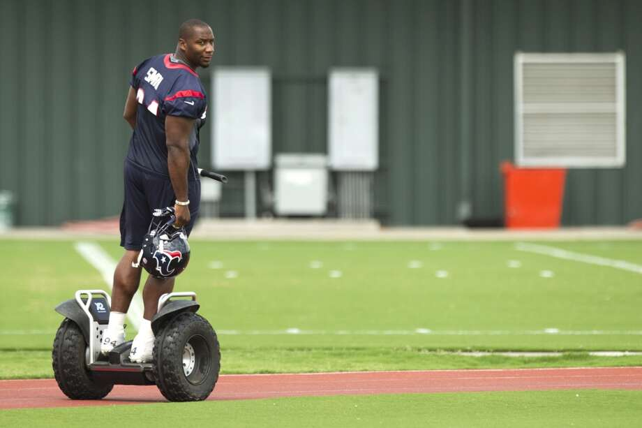Texans defense end Antonio Smith rides a Segway across the practice field.