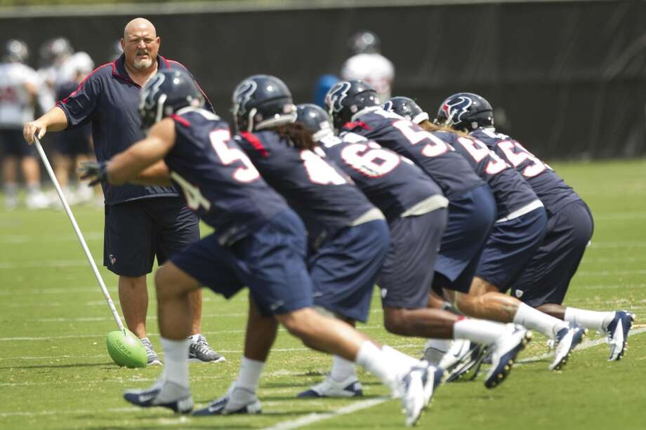 Texans linebackers coach Reggie Herring runs his group through a drill.