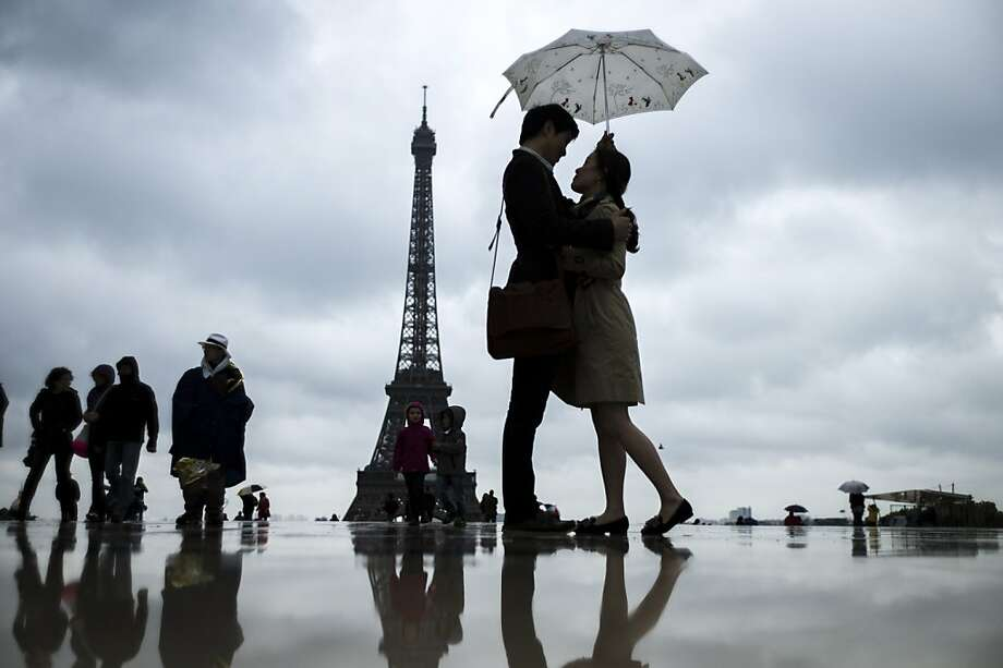 TOPSHOTS People gather on the Trocadero Square in front of the Eiffel Tower on a rainy day, on May 20, 2013, in Paris. AFP PHOTO / FRED DUFOURFRED DUFOUR/AFP/Getty Images Photo: Fred Dufour, AFP/Getty Images