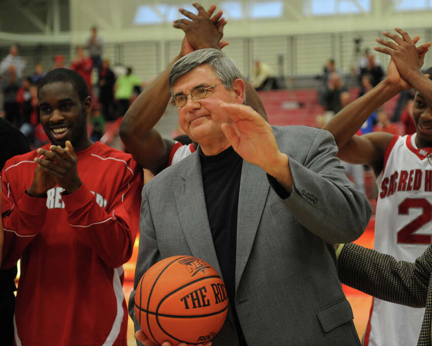 Sacred Heart men's basketball coach Dave Bike accepts the game ball and acknowledges the crowd after his 500th career victory at the Pitt Center at Sacred Heart University in Fairfield on Sunday, January 2, 2011.