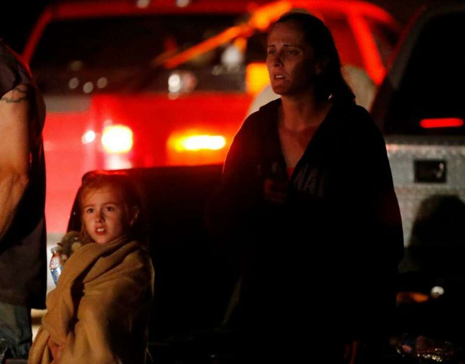 Seven-year-old Katrina Ash, left, watches with her mother, Amber Ash, right, as heavy equipment is brought into their tornado damaged neighborhood near Dale, Okla., Sunday, May 19, 2013. Residents are not being allowed into the neighborhood as search and rescue operations continue.