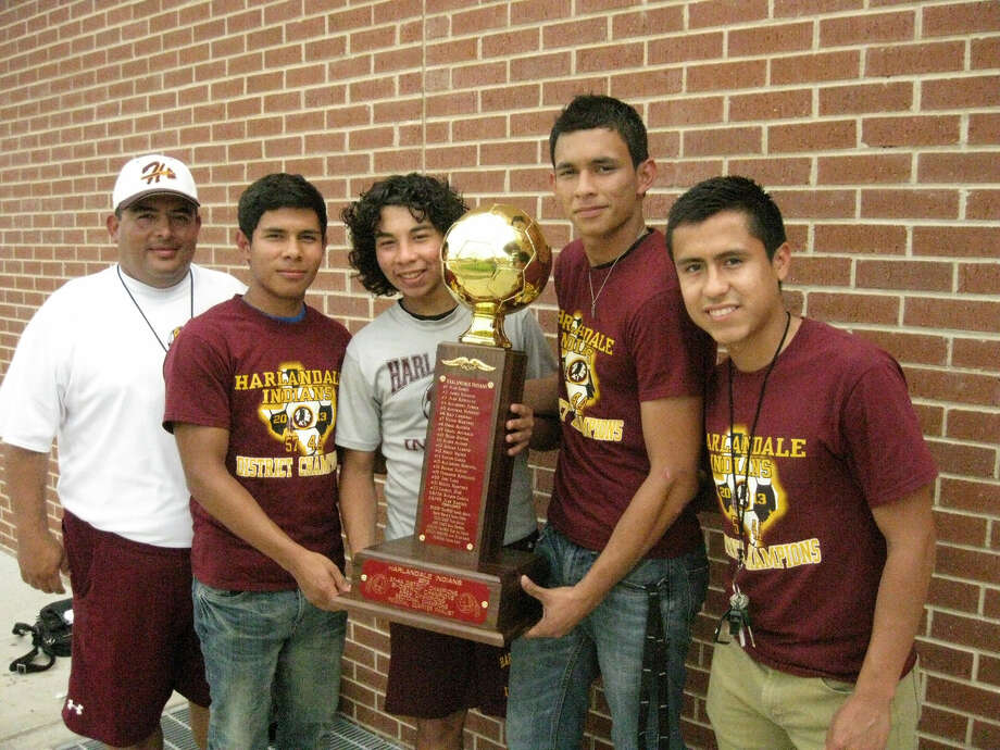 From left, Harlandale soccer coach Frank Aguilar, Rigo Cardenas, Angel Valdes, Alejandro Zuniga, and Victor Martinez with their third-straight district championship trophy. The team was a quarterfinalist in the 4A district playoffs.