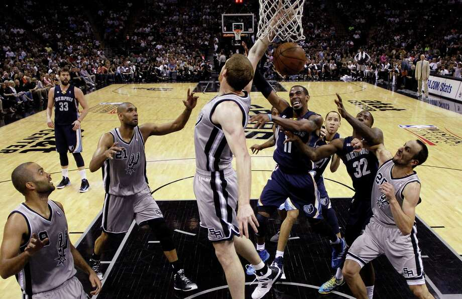 Memphis Grizzlies' Mike Conley (11) is defended by San Antonio Spurs' Matt Bonner, center, as he tries to score during the first half in Game 1 of a Western Conference Finals NBA basketball playoff series Sunday, May 19, 2013, in San Antonio. (AP Photo/Eric Gay) Photo: Eric Gay, Associated Press / AP